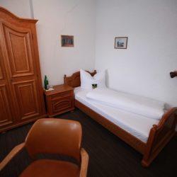 Einzelzimmer - Blick auf Bett, Kleiderschrank und Tisch