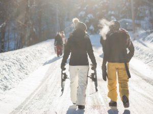 Schneeschuhwandern - zwei Personen im Wald mit Schneeschuhen in der Hand