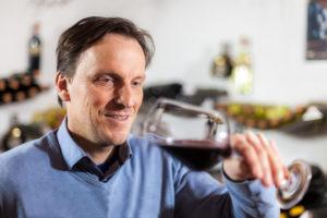 Leiter des Weinseminars mit einem Rotwein